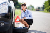 Conceptual photo of woman with a flat tire — Stock Photo