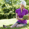 Smiling woman with tablet pc is sitting on the grass while smili — Stock Photo #28248053