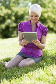 Smiling woman with tablet pc is sitting on the grass while smili — Stock Photo
