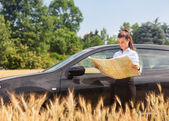 Woman lost with car in a corn field and looking at the map — Stock Photo