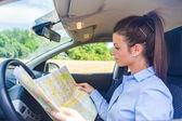 Femme cherche à une carte à l'intérieur de sa voiture — Photo
