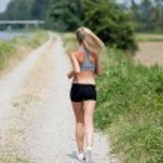 Beautiful blonde woman running along the riverside — Stock Photo