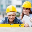 Two Female Constructors are working with a level — Stock Photo