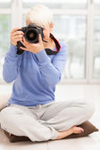 Female photographer with DSLR at home sitting on the floor — Stock Photo
