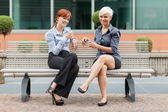 Businesswoman sitting outside on a bench and talking — Stock Photo