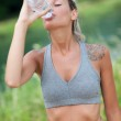 Young woman is drinking water after running session — Stock Photo #29997357