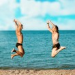 Happy gay couple jumping in front of a beach  — Stock Photo