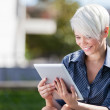 Businesswoman outside in a park with tablet pc — Stock Photo