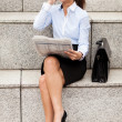 Brunette Businesswoman sitting on stairs with newspaper — Stock Photo