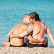 Gay couple is kissing in front of the beach — Stock Photo