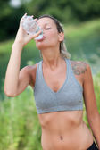 Young woman is drinking water after running session — Stock Photo