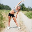 Smiling blonde woman is stretching on a field street — Stock Photo #30000957