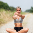 Smiling blonde woman is stretching on a field street — Stock Photo #30001153