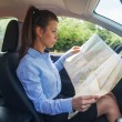 Woman is looking at a map inside her car — Stock Photo