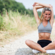 Smiling blonde woman is stretching on a field street — Stock Photo #30001459