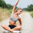 Smiling blonde woman is stretching on a field street — Stock Photo
