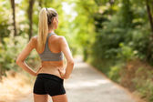 Sexy female with tonic bottom looking at running path — Stock Photo