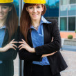 Smiling female consructor next a glass building — Stock Photo