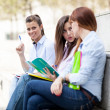 Stock Photo: Three female students sitting on a bench with notebooks