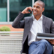 Afro American manager sitting on the bench and phoning — Stock Photo #31513497