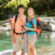 Portrait of couple with trekking outfit standing next to lake — Stock Photo