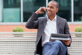 Afro American manager sitting on the bench and phoning — Stock Photo