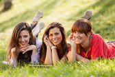 Three woman sitting on grass and looking at a digital tablet — Stockfoto