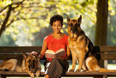 Woman is sitting on a bench with two german shepherds — Stock Photo