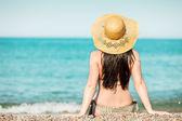 Mulher sentada na costa de mar, enquanto olha para a água — Foto Stock