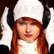 Red hair woman with winter outfit listening to music — Stock Photo