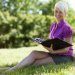 Smiling blond woman sitting in a park — Foto Stock