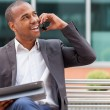Successful african businessman phoning while smiling — Stockfoto