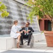 Stock Photo: Smiling Businessmon wheelchair looking towards his doctor
