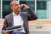 Successful african businessman phoning while smiling — Stock Photo