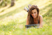 Pretty Brunette girl on the grass is looking a digital screen — Stockfoto