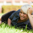 Blonde Smiling woman laying on a grass field — Stock Photo