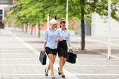 Two businesswoman are walking on the street — Stock Photo