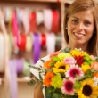 Beautiful smiling florist with colorful bouquet — Stock Photo