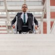 Businessman on wheelchair in front of stairs — Stock Photo