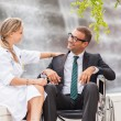 Stock Photo: Female Doctor is talking to businessmon wheelchair