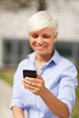 Portrait of blonde businesswoman with mobile phone — Stock Photo