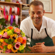Smiling florist next to a coloful bouquet — Stock Photo