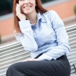 Red hair Businesswoman is sitting on a metal bench and phoning — Stock Photo #34497493