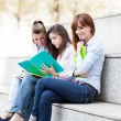 Three female students sitting on a bench with notebooks — Foto de Stock