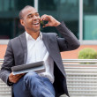 Afro American manager sitting on the bench and phoning — Stock Photo #34504705