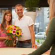 Happy smiling couple at the flower shopt with a bunch of flowers — Stock Photo