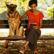 Woman on a bench with digital tablet and dog — Stock Photo