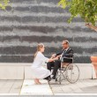 Female Doctor is talking to businessman on wheelchair — Stock Photo