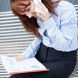 Red hair Businesswoman is sitting on a metal bench and phoning — Stock Photo #35753597