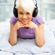 Blonde woman listening to music with headphones in the bed — Stockfoto
